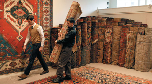 Employees Daniel Larkin (left) and Brian James remove an antique rug from one of several showrooms at Claremont Rug Co. in Oakland. The business, which began with a 40-rug inventory in 1980, now has about 3,500 carpets in stock.