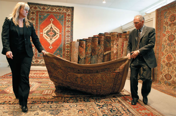 Nancy Brinkley helps Jan David Winitz unfurl an antique rug at his Claremont Rug Co. in Oakland. Winitz, who founded the business in 1980 with his wife, has become one of the world's leading sellers of antique Oriental rugs.