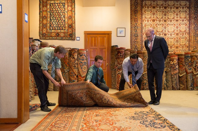 Mr. Winitz observes employees Austin Pence (left), Eric Moore and Alex Bonilla as they unroll a late 19th-century Persian Hadji Jallili Tabriz carpet in the Claremont Rug Co. showroom.