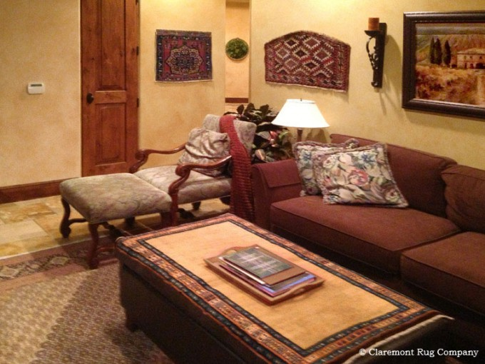 Tribal Antique Persian Oriental Collectible Rug on Wall and antique Persian Bakshaish rug on a table in a lounge
