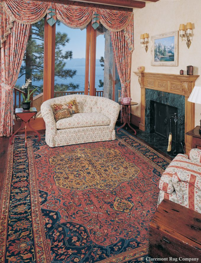 An collectable Ferahan Sarouk antique carpet is the focus of a sitting area in this master suite