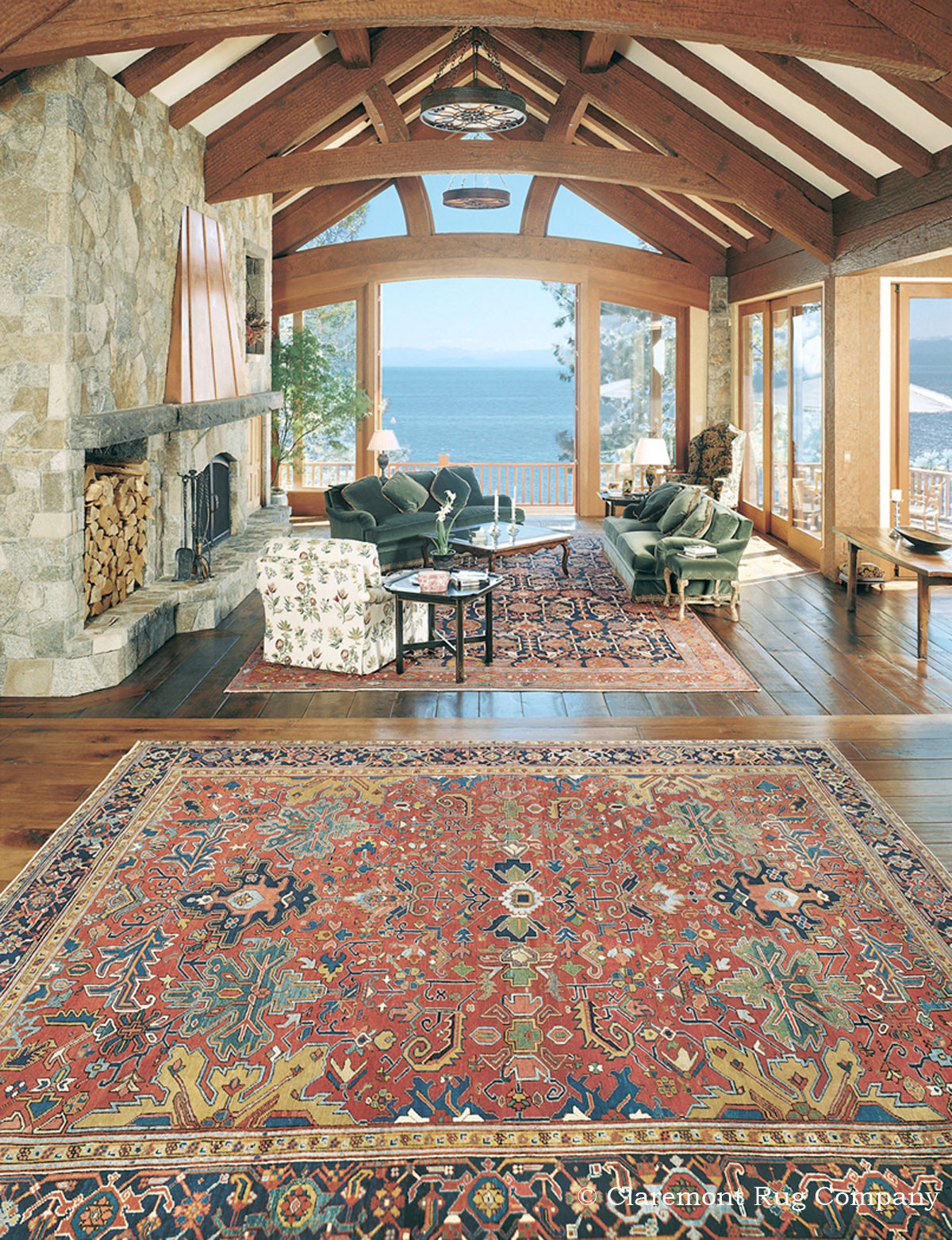 In this gracious lakeside family compound, two unique village carpets, a 19th century Serapi (foreground) and a 19th century Malayer (background) bring a sense of unity and warmth to the broad vistas that can be seen from this high-ceiling room.