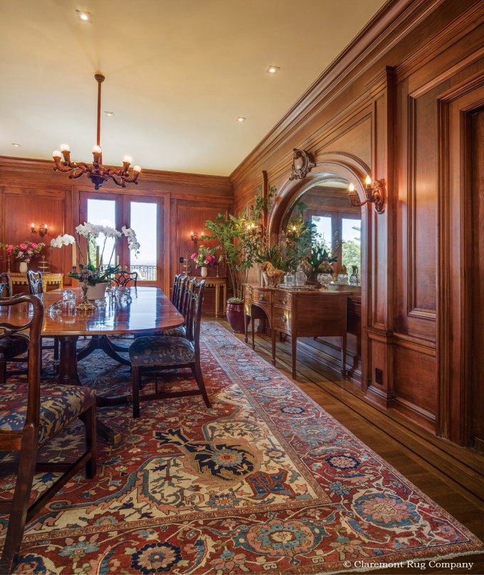 Persian Serapi Antique Rug in a traditional dining room with grand wood paneling