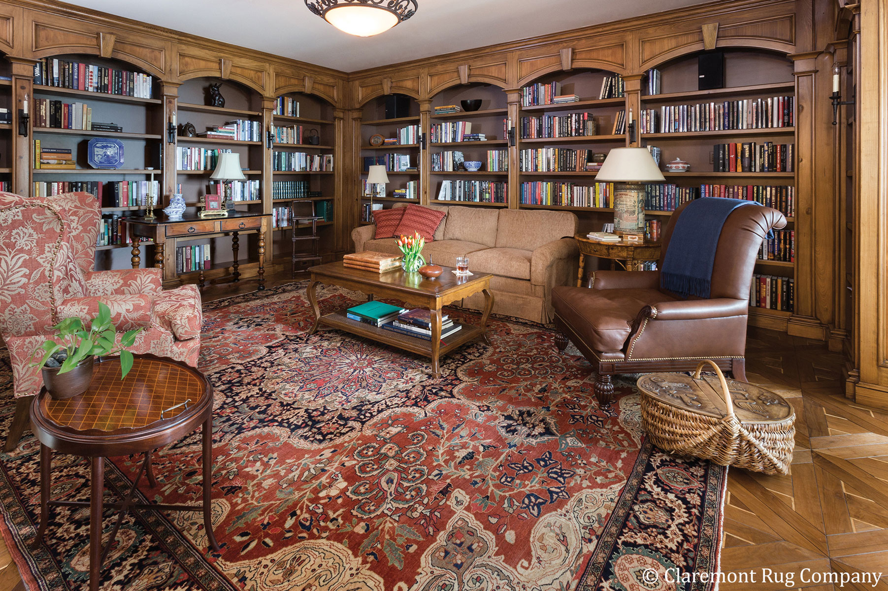 A grand Persian Ferahan Sarouk (circa 1875) provides the fitting foundation for the Houston home's genteel library. This rare rug's incredible intricacy provides an ideal note of refinement with its warm, time-softened colors that perfectly complement the handcrafted wooden bookcases. (Decor: Marianne Michaels Interior Design.) width=