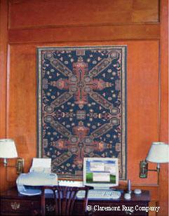 This collectible tribal rug from the Caucasus Mountains is utterly striking displayed on the wall of an executive's home office.