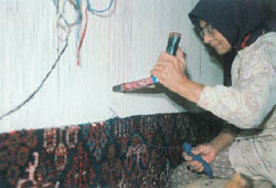 iranian woman weaving a Persian carpet