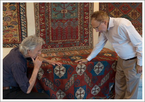Rug collector for over 40 years examining an extremely rare 170-year-old Caucasian Pinwheel Kazak with Jan David Winitz.