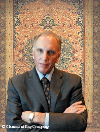 Winitz stands in front of an antique Persian rug from around 1850.
